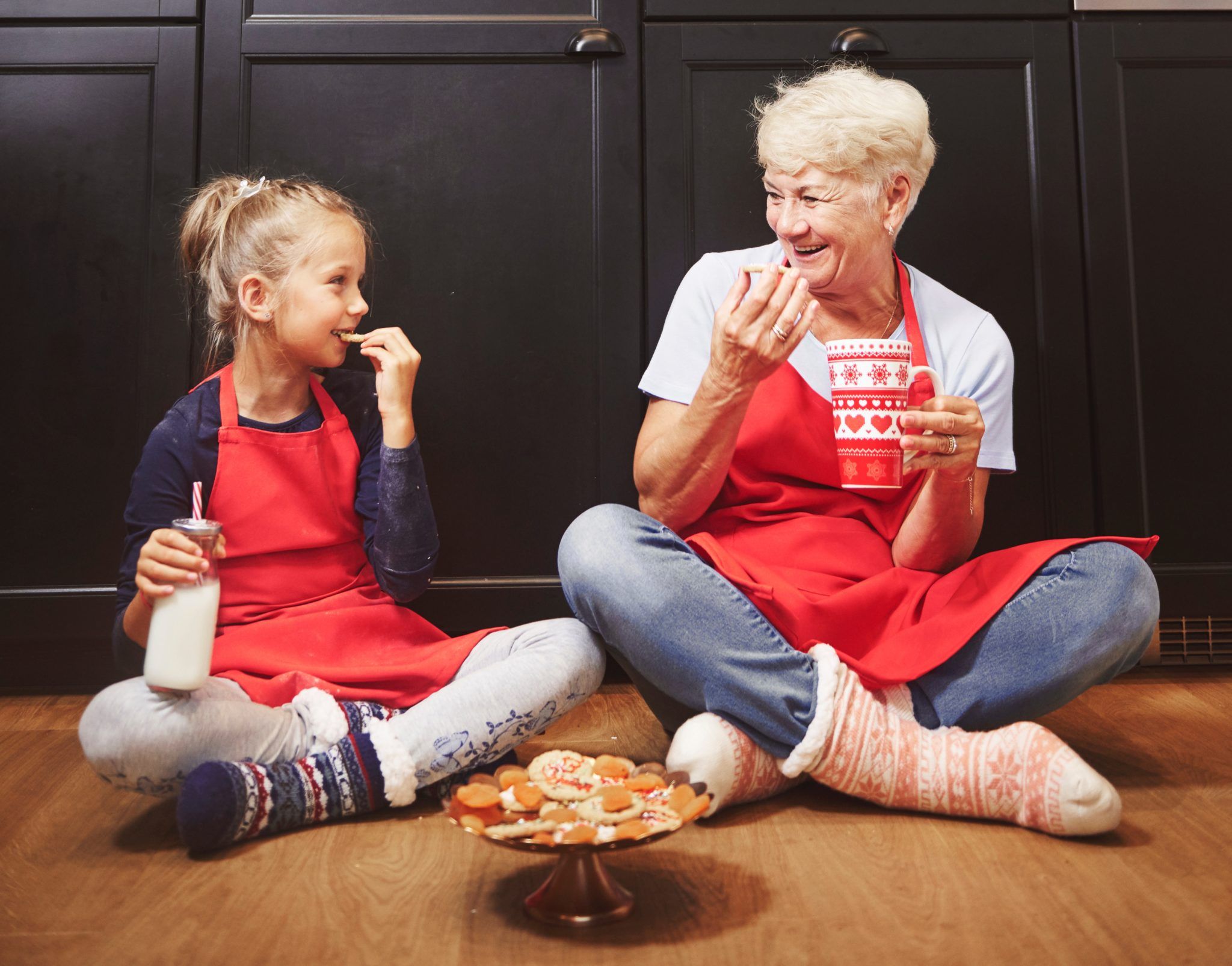 Girl and grandma eating Christmas cookies on the floor