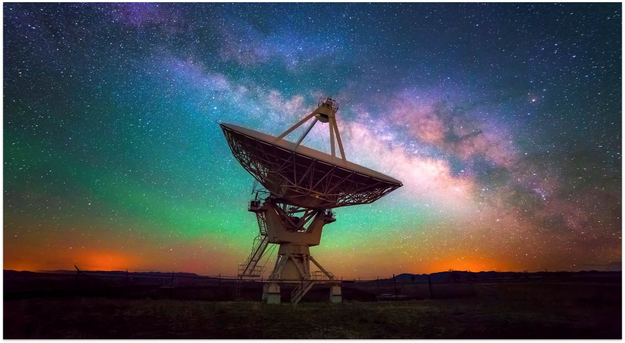 Signal dish in front of a starry, colorful sky