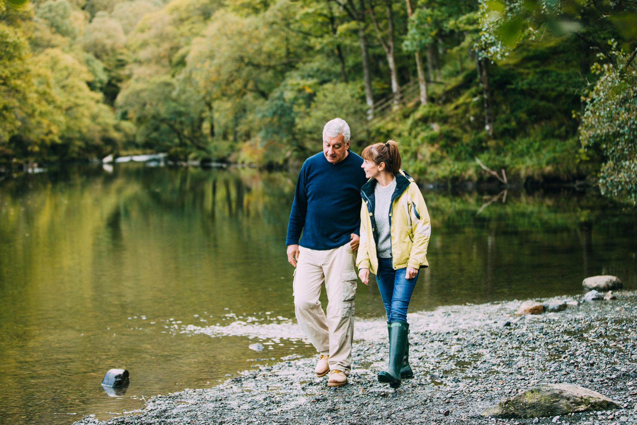 Couple walking on a lake shoreline