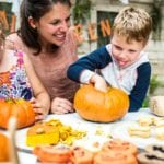 Mother and two children carving pumpkins