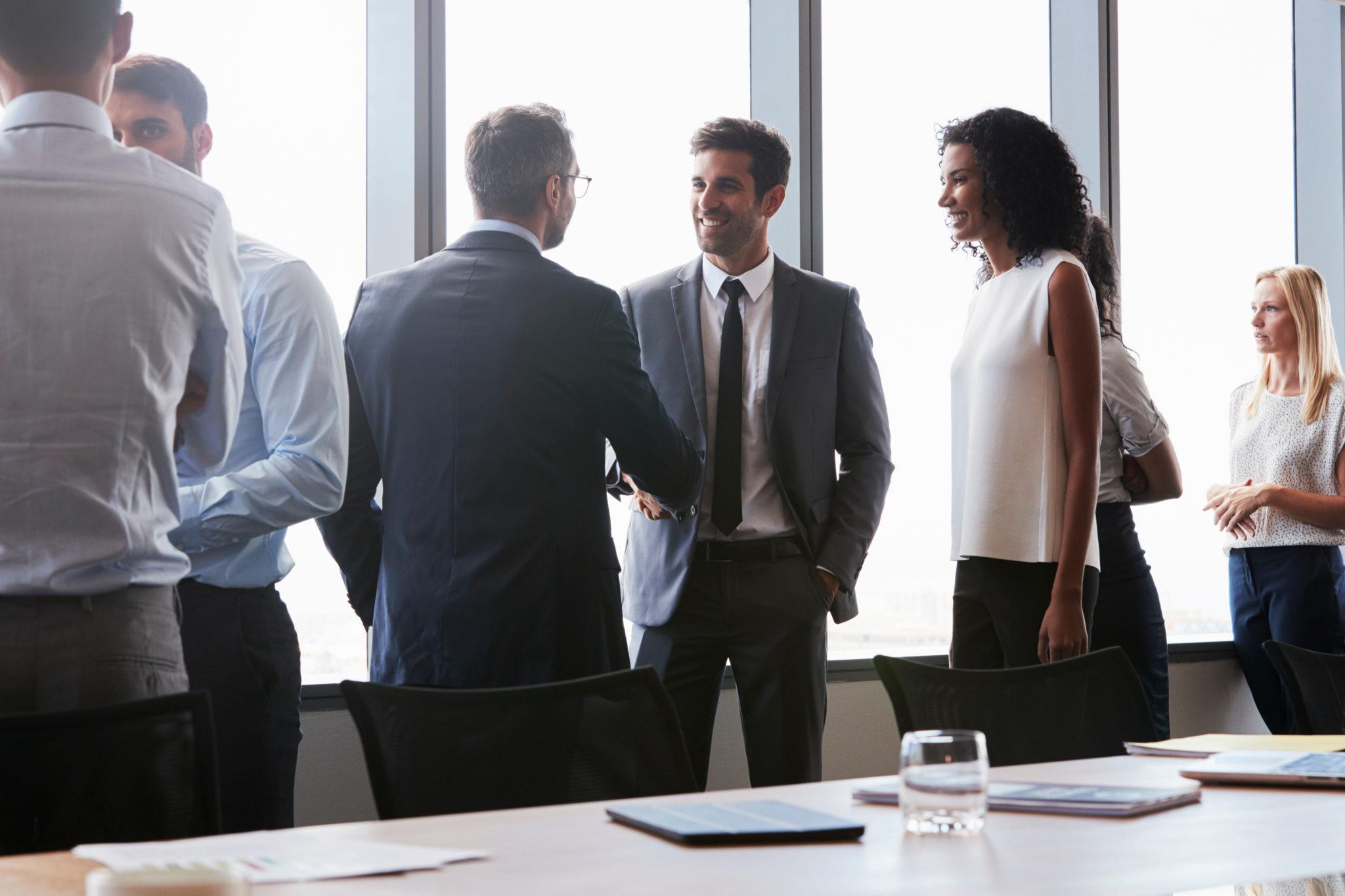 Businesspeople Shaking Hands Before Meeting In Boardroom