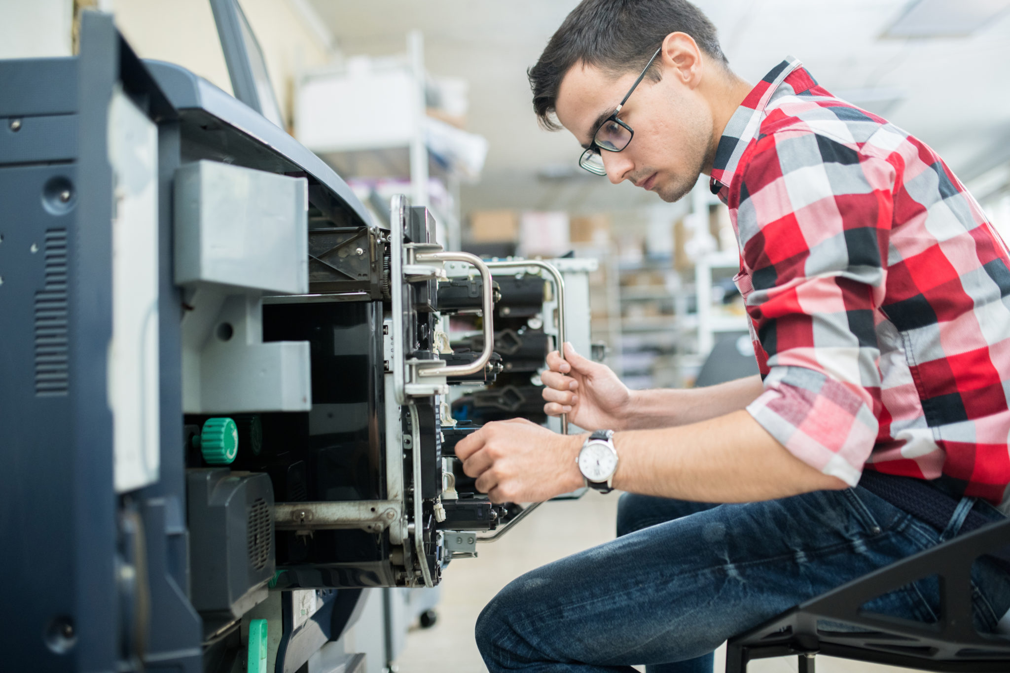 Side view of casual man working with modern printing equipment in typography office