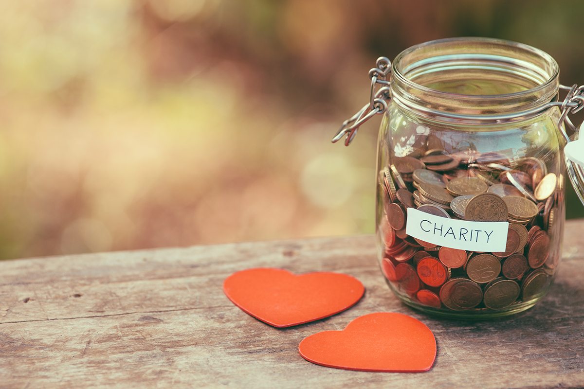 Money jar full of coins for charity and a couple of handcrafted wooden heart shapes. Shallow depth of field. Shot with Canon EOS 5D mark ii.