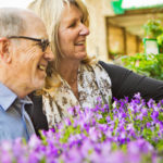 older people sniffing flowers