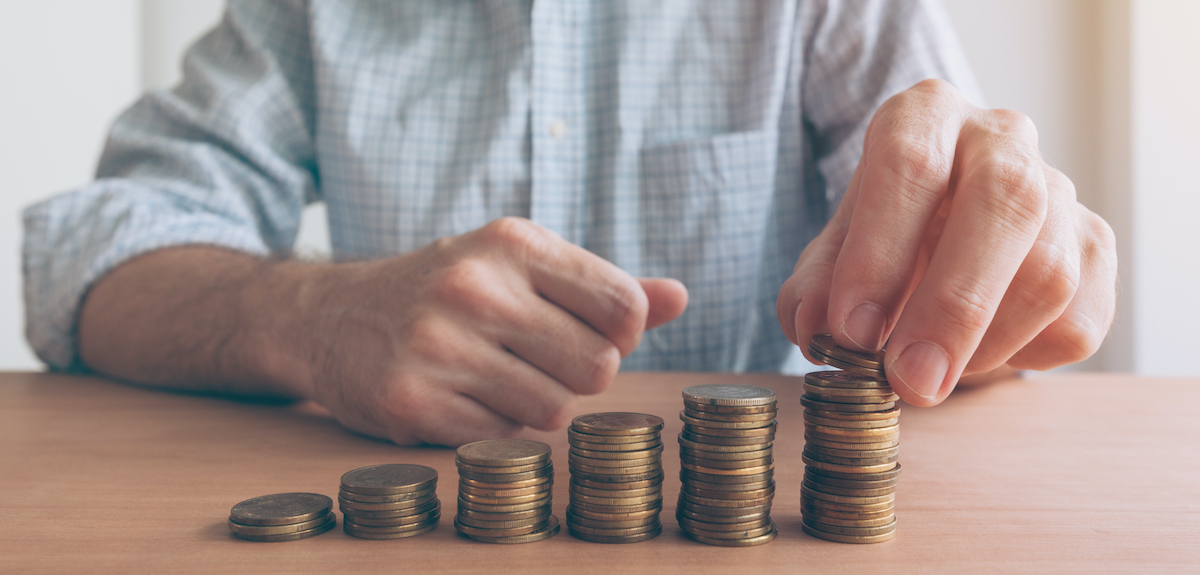 Finances and budgeting, businessman stacking coins on office desk