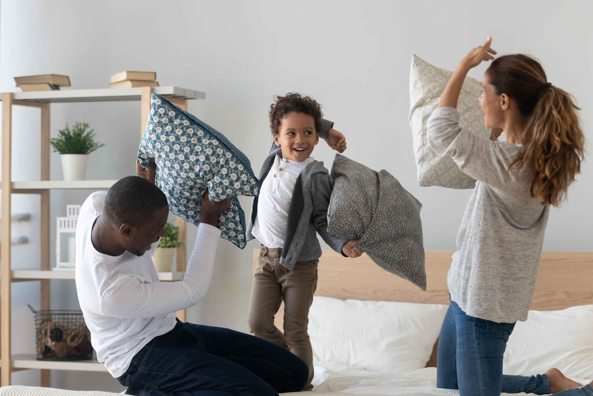 family having a pillow fight on their bed