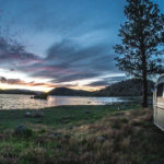 airstream parked on a lake with a beautiful sunset