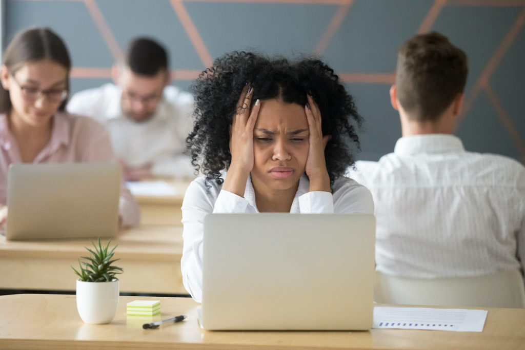 Tired black female employee stressed by lots of workload to do, desperately looking at laptop screen, upset African American worker feeling down losing money in online game or becoming bankrupt