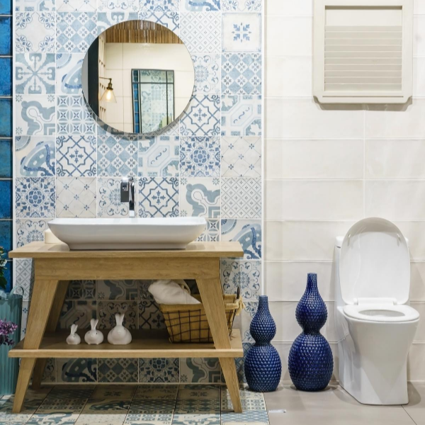 bathroom with toilet and wooden sink a round mirror and blue pattered wallpaper