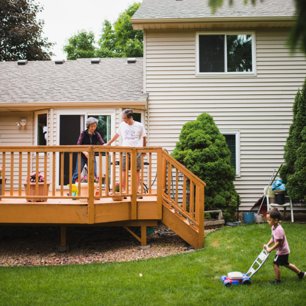 deck with people on it and a little girl playing in the yard