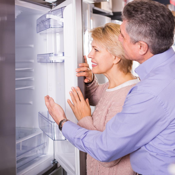 lady and a man looking at a refrigerator smiling