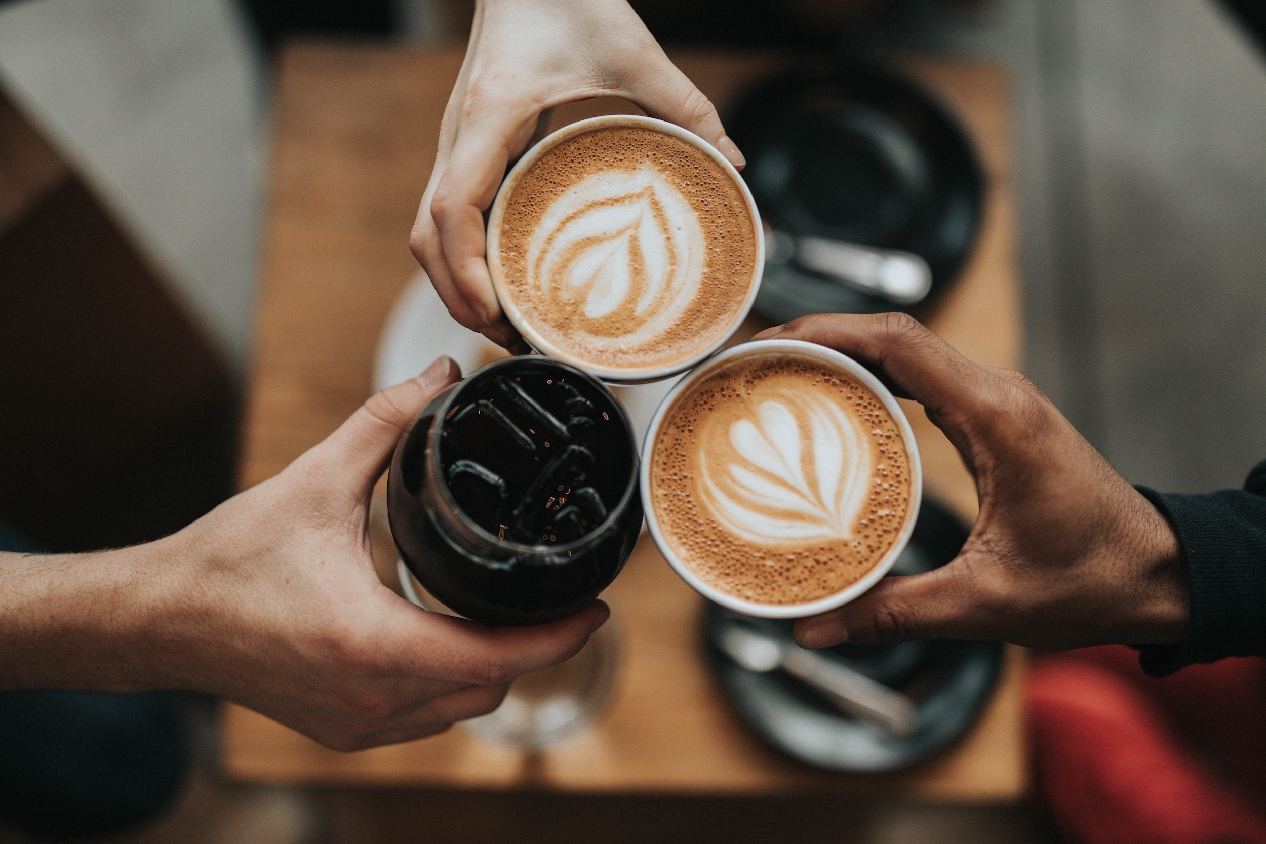 people holding up cups of coffee in a circle