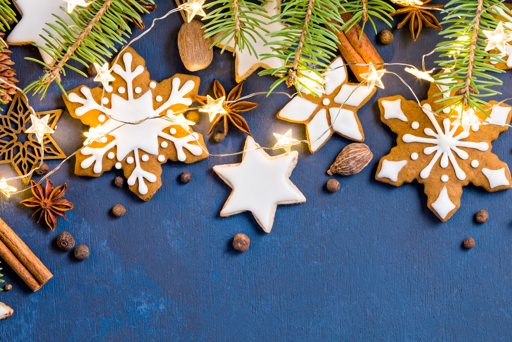 blue background with iced snowflake shaped cookies, greenery,