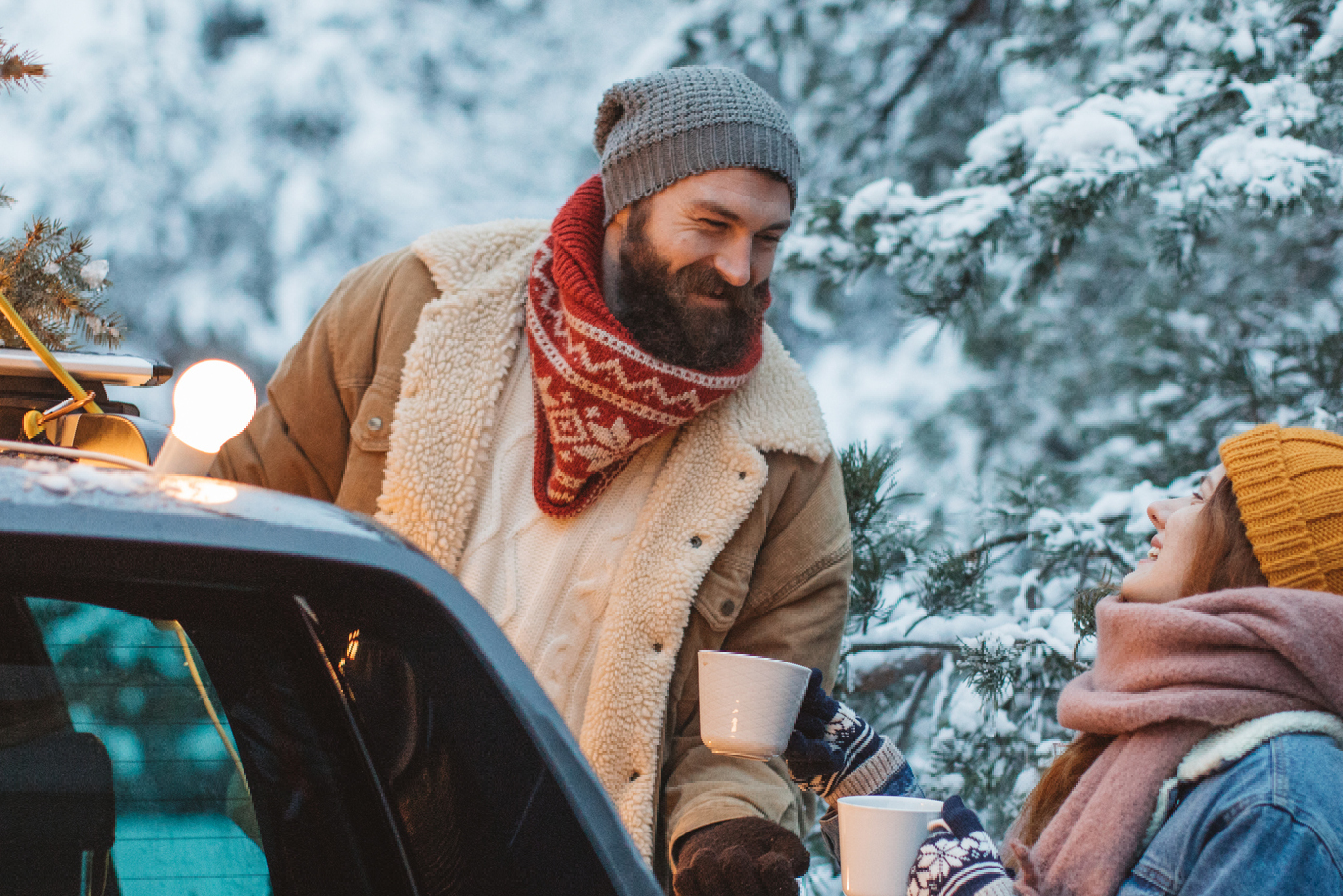 two people bundled up in the snow with a car
