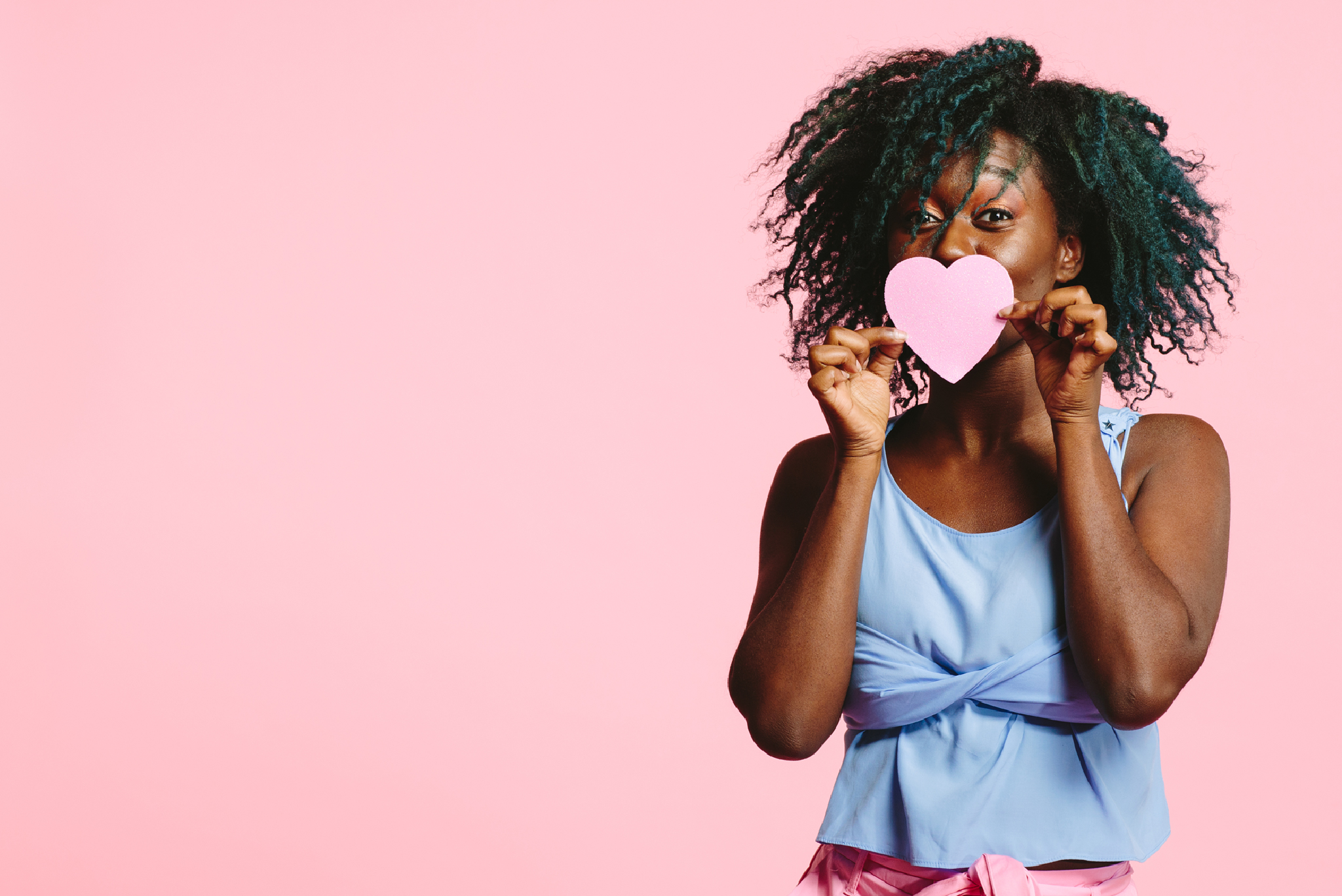 woman kissing pink paper heart
