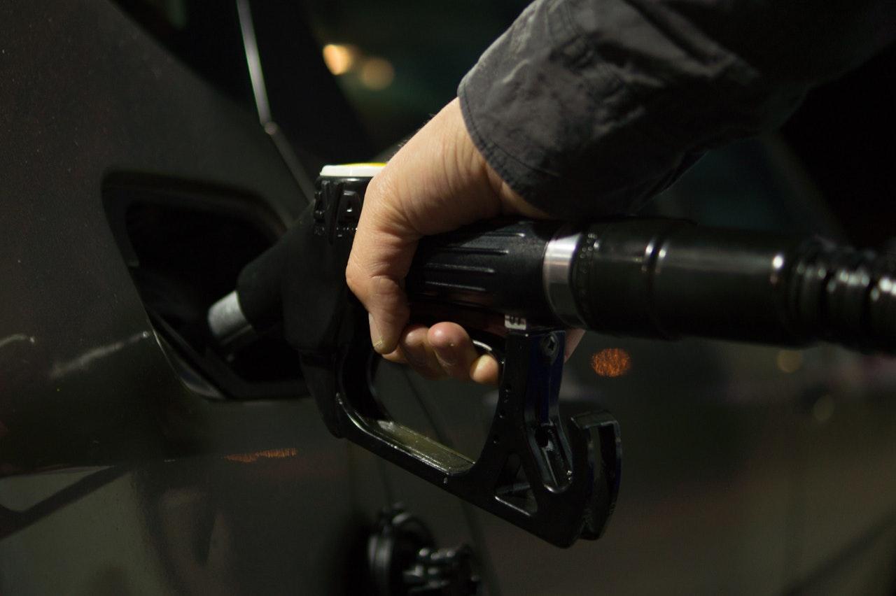 hand gripping a gas pump putting pump in car