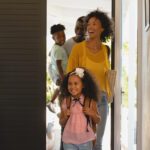 young happy family looking excited and awed as they enter a home