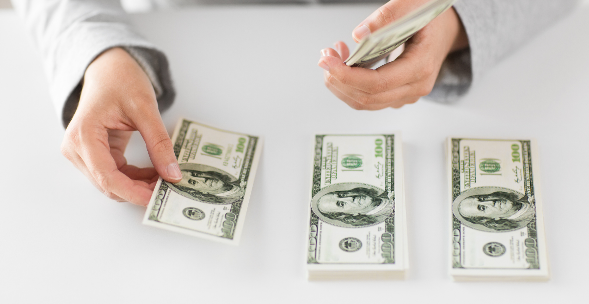 woman's hands stacking bills on a white table