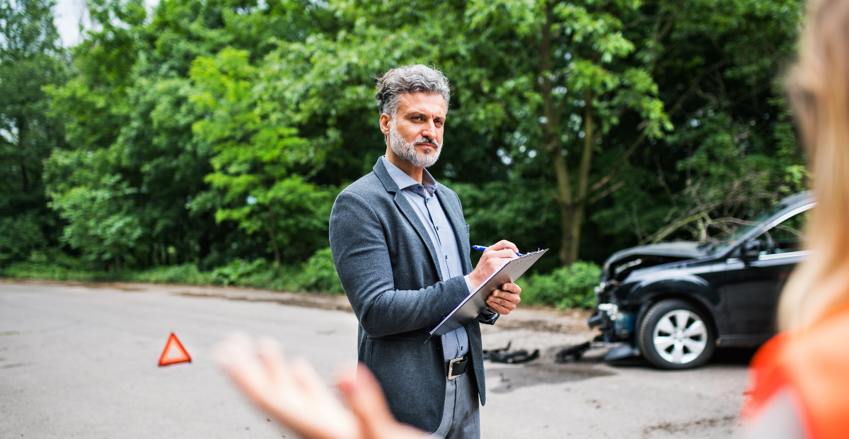 stern man with clipboard in front of wrecked car and exasperated woman