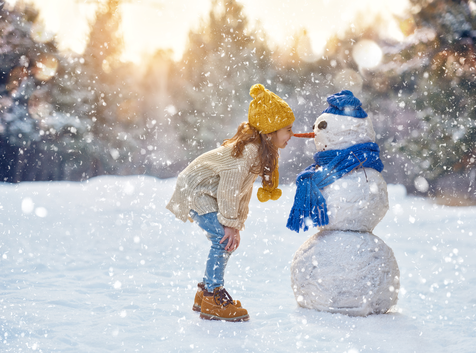 Holiday SKip-A-Pay 2021 image of girl nose-to-nose with a snowman